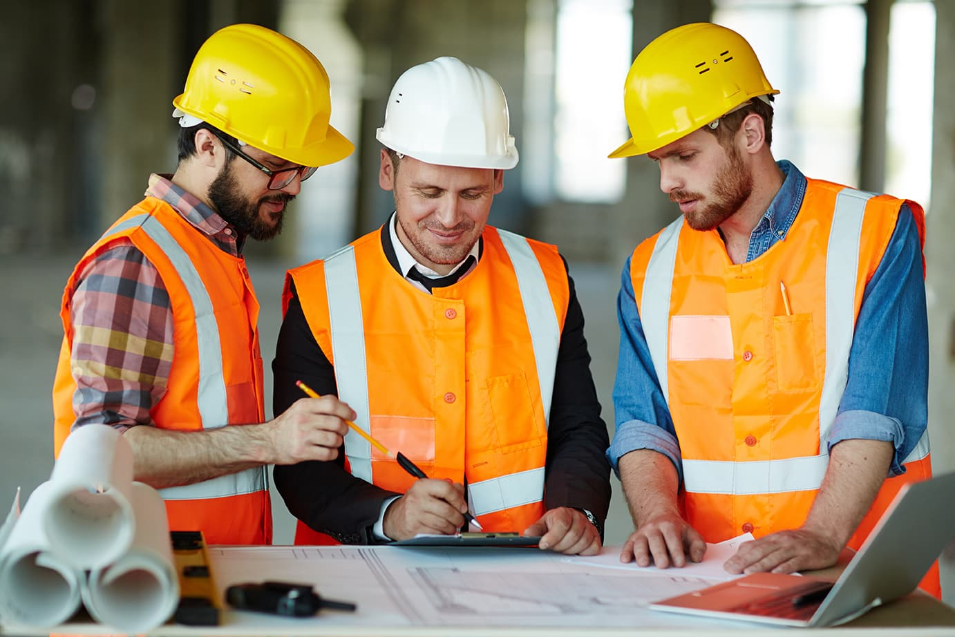 construction manager and workers review plans